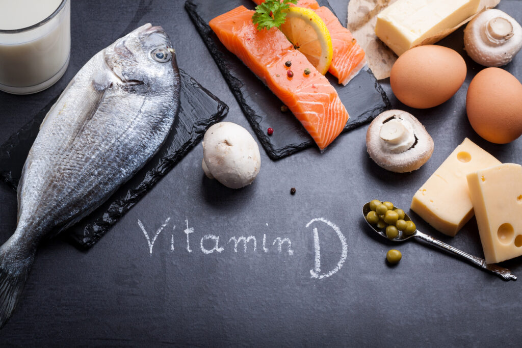 Black slate table with product rich in vitamin D and omega 3. Written word vitamin D by white chalk